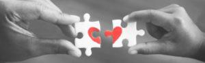 manos armando rompecabeza con dibujo de corazón
